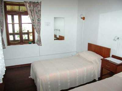 The Coach House, bedroom: An open-plan studio flat with timbered verandah and a well-screened twin-bedded sleeping area